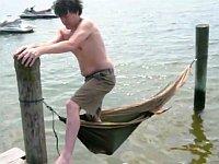 どうしても水の上のハンモックに乗りたい男性
