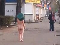 頭にたらいを被り手に包丁を持って側道を歩く全裸女性