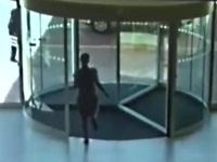 回転ドアに勢いよくぶつかる女性
