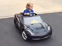 カスタムされたオモチャの車で運転する3才の女の子