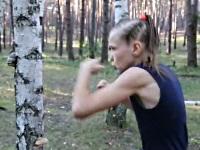 素早いパンチを繰り出して白樺の木を殴る女の子