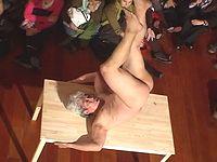 日本人芸術家が全裸でテーブルと交じり合う奇妙なパフォーマンスをご覧ください...