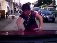 執拗に車を追いかける当たり屋のオバサン