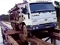 丸太を積んだ大型トラックが危険な橋を横断するよ