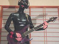 ラバースーツを着てアナルにディルドを挿れた女装子ギタリストの演奏が意外に上手いwww